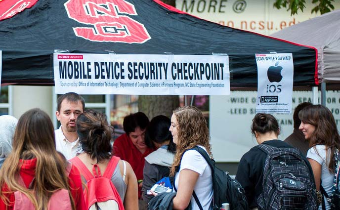 Darren Fallis of OIT Security and Compliance talks with iOS device users at the Mobile Device Security Checkpoint.