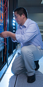Staff member patching in equipment in data center